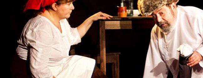 Dos personajes de La Luciérnaga arrodillados en escena junto a una mesa con una botella: ella, a la izquierda, lleva un pañuelo rojo en la cabeza y un delantal blanco; él, a la derecha, lleva un sombrero de piel estilo eslavo, y su rostro se dirige al público