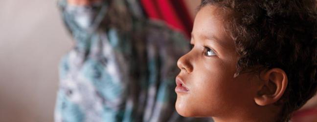 Fotografía de un niño con la mirada perdida y al fondo una mujer desenfocada vistiendo el velo islámico