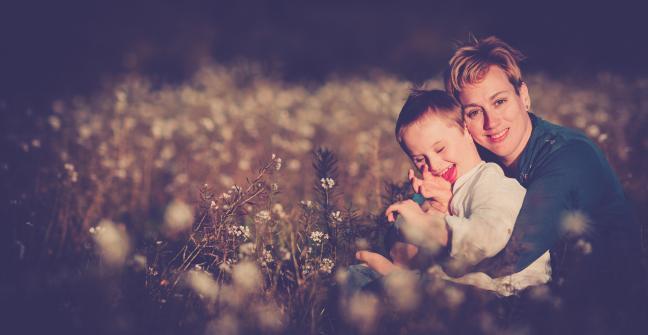 Imagen del niño Ioan Inchusta sonriente, en el campo, abrazado por su madre