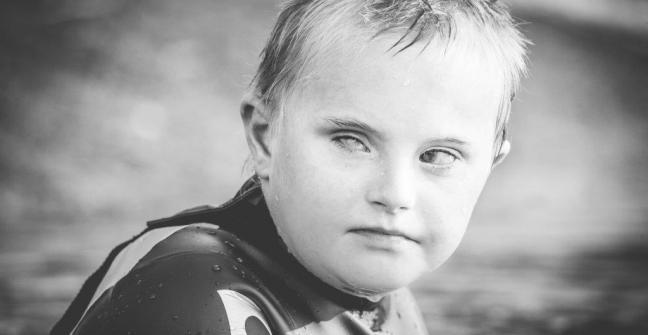 Fotografía de un niño con el pelo y la cara mojados por haber estado nadando